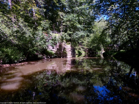 Looking upstream toward the ruins of a Civil War era railroad bridge that used to cross Pope's Head Creek, Chapel Road Park, Fairfax County, Virginia USA.