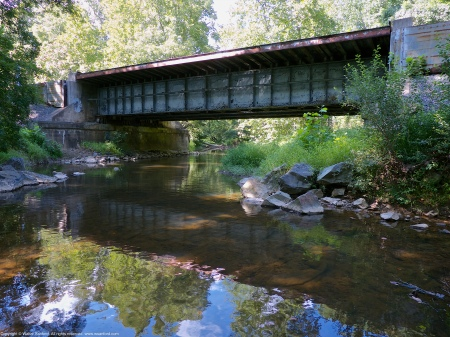 Looking downstream toward modern era railroad bridge that crosses Pope's Head Creek, Chapel Road Park, Fairfax County, Virginia USA.
